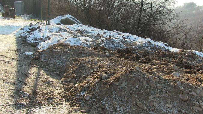 Excavated fill-in material - some of it covered by snow - outside Ravne Tunnel Labyrinth, December 27, 2014. Photo by Jock Doubleday.